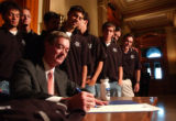 (Denver, Colo., May. 12, 2004) Gov. Bill Owens signs then presents soccer players and coaches of...