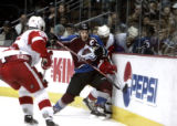 Joe Sakic, left, checks Detroit Red Wings player Chris Chelios, right, in the first period of play...