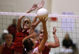 No. 1, Eaglecrest's Courtney Karst, #1, and Jordan Kissman, #11 jump up at the net for the block...