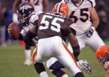 Denver Broncos quarterback Jake Plummer , left, is chased after Cleveland Brown Defender Willie...