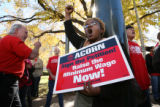 MJM662   Quianna Ray (cq), 26, center, of Denver holds a sign supporting an increase in the...