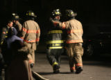 Two Denver fireman walk away from a house at 2349 Poplar St. Sunday night October 22, 2006 in...