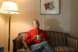 Peter Russell (cq), on the couch with a cup of tea just after eye surgery. He is the director of...
