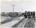 Onlookers crowd about the railroad tracks near the wreckage of a school bus in which 20 children...