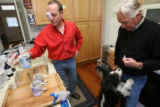 Peter Russell, (cq), makes tea in his home with Stephen Crout, (cq), and one of their eager dogs...