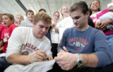 (L-R) Avalanche forward Paul Stastny and goalie Peter Budaj,  sign a shirt after working out with...