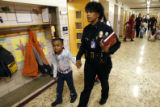 DLM03100   Commander Tracie Keesee with the Denver Police is led into class by first-grader Alexia...