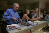 Bill Ritter cuts up a steak as wife Jeannie, sons Sam and August look over a political web sit at...