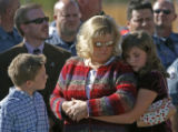 Julie Holiday stands with her children Hunter, CQ, 8, left, and Savannah, 10, right, as a flock of...