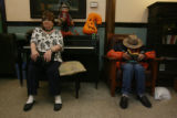 Elfreide Beall, (cq), sits upon the piano bench while Larry Miller (cq), reads a western cowboy...