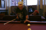 Jimmy Vance plays pool. His friends, left, Larry Miller, and Rebecca Simon eagerly watch his...