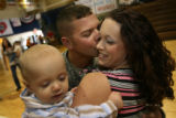 MJM160   Shayna Brawley (cq), gets a kiss from her husband, E-5 Dustin Brawley as she holds their...