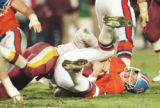 (DENVER, COLO., JANUARY 31, 1987) Denver Broncos quarterback John Elway is sacked by a Whashington...