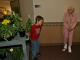 Jack Cameron, 8, pulls his plant cart toward Helen Biere (cq), right, to give her a plant, Monday...