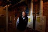 Home builder John Keith (cq) stands next to some tankless water heaters in one of his homes in the...