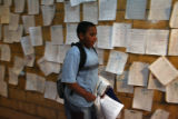 Student Oloyea Wallin (cq), 12, walks past a wall that posts examples of good work by students....
