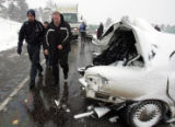 Paramedics escorts an injured man to an ambulance after she was involved in a 25 car pile up, on...