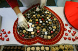 Stephany's Chocolates employee Fabiola Martinez (cq) of Denver assembles a heart-shaped box of...