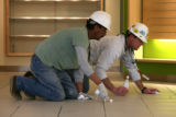 Juan Ruiz, cq, and Keith Schmitt, cq, of PCL Construction, seal tile grout Monday Feb. 19, 2007 at...