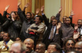 An overflow crowd of local taxi drivers, raise their hands in response to  Buffy McFadyen's, (the...