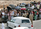 XAL107 - Bahama's residents and tourists look at the arrival of the hearse carrying Anna Nicole...