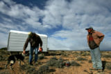 (DLM8311) -  Ernie Etchart, 43, left, pets one of the herding dogs as he pays a visit to Lucho...