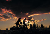 A pair of mountain bikers enjoy the single track trails and sunset views from the top of Vail...