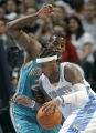 Denver Nuggets' Carmelo Anthony drives past New Orleans Hornets Desmond Mason in the 106-91...