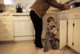 Jimmy Cathey, 14 months, slips into his grandmother Caroline Cathey's cabinet on February 17,...
