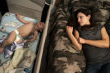 Katherine Cathey (cq) lies down on her husband's Jim Cathey's boyhood bed while their son Jimmy...