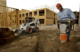 ( DENVER COLO. 8/18/04   Plumber Viktor Khomyakov, rt,  tamps down soil to prepare it for concrete...