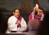 Deacon Maniuel Ramirez, left assists as father Miguiel Guzman prepares the host during morning...