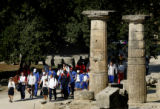 (OLYMPIA, GREECE, AUGUST 18, 2004) Competitors in the Athletic's men's shot put march past column...