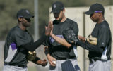 Colorado Rockies'  LaTroy Hawkins, left, compares hand sizes with teammate Jason Hirsh, center,...