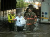 (DENVER, Colo., Aug. 18, 2004)    Maria Dowdy is helped through flood waters by emergency workers...