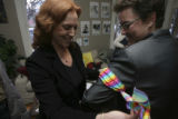 Ilene Blum, (cq), left, Director of Volunteers, ties a ribbon on Blake Weber, (cq), right,...