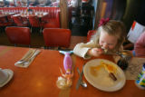 Rachel DeWitt, 4, of Littleton, and her mermaid, Twinkle, enjoy eggs and sausage at the counter at...