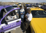 Cab drivers wait in the taxi holding lot at DIA to get their turn for a fare at the airport Monday...