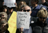 A man attending a rally holds a sign Monday February 26, 2007 with scores of health care consumers...