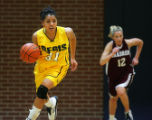 Regis University's Diana Lopez (#31) pushes the ball up court as Chadron State's Tera Schmid (#12)...