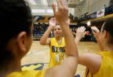 Regis University's Denise Lopez (#43, center) high fives her twin sister Diana Lopez (#31, left)...