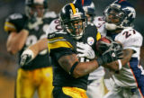 The Pittsburgh Steelers Willie Parker (#39, RB) tries to spin away from the Denver Broncos Darrent...