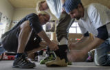 Larry Houchen (cq) left, and  employee Michael Block (cq) right,   fit a custom boot insert for a...