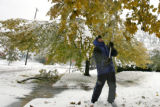 DLM00025   Dave Lopez, 61, knocks the heavy snow from the tree in his front yard in hopes of...