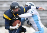 MJM266  Wheat Ridge High quarterback Dylan Orms, left, tries to avoid Ralston Valley High's Mike...