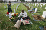 Military mom Doyla Lundstrom (cq, center) of Broomfield lays out flowers she brought to leave at...