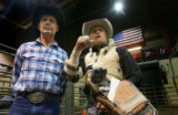 Glen Ford, left, and his son Heath Ford, wait in the chutes before Heath's bareback ride at the...