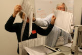 Andrea Skeen and Marry Ann Thompson, run ballots through an optical scanner as counting of...