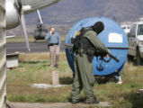 Photo by Dean--A swat team member locks and loads at the Garfield County Airport where a command...