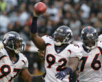 Demetrin Veal, left and Kenard Lang, right, celebrate a fumble recovery by Elvis Dumervil, center,...
